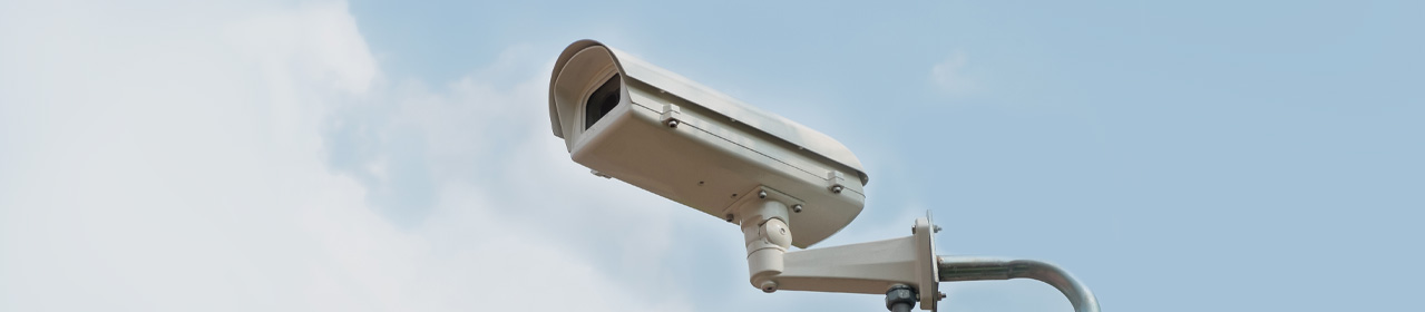 photo of a security camera against blue sky